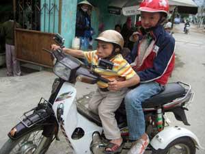 Phuong, 30 ans, responsable du Centre de soutien aux victimes de l'agent orange de Da Nang, conduit un enfant victime de l'agent orange au marché sur sa moto